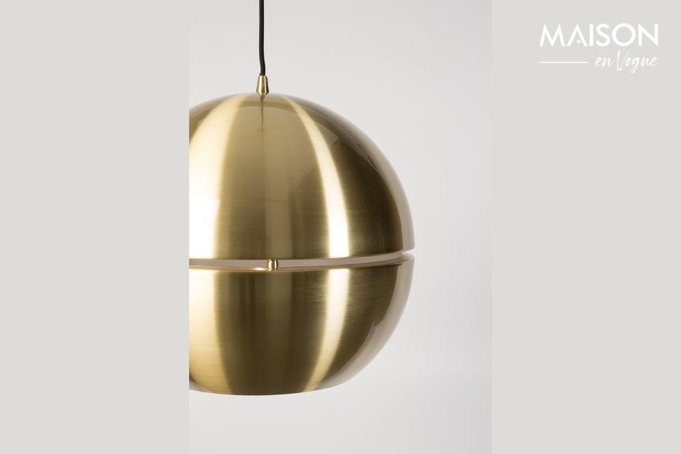 Su forma redonda y el brillo de la chapa de latón se ven realzados por la fina abertura horizontal