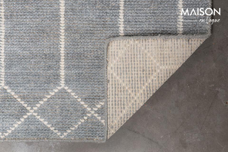 Está vestida con formas geométricas entrelazadas cuyo color claro contrasta con el fondo gris