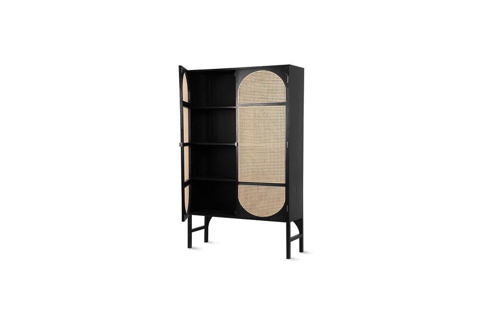 Este armario de madera negra y mimbre de color natural es una invitación a viajar