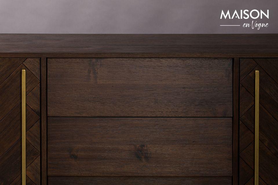 El aparador tiene 3 cajones centrales y a cada lado 2 puertas con dibujos de chevrones en la madera