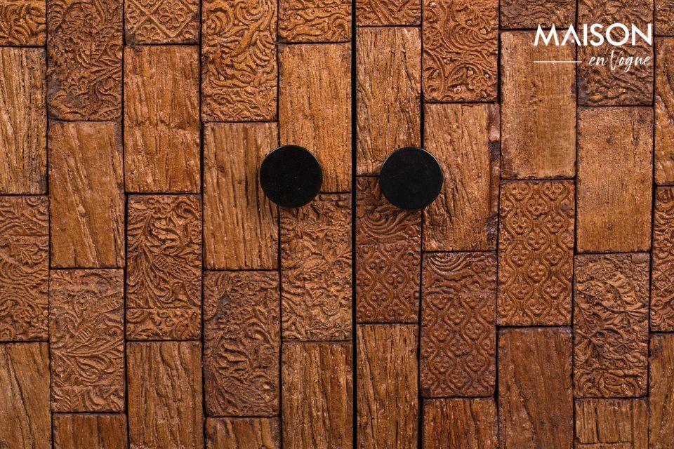 El frente está hecho de dos pequeñas puertas de madera talladas en un hermoso estilo de