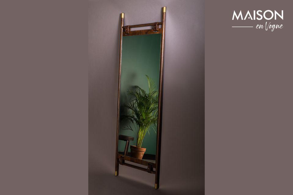 El espejo que flota en el centro del marco está sujeto por correas de cuero