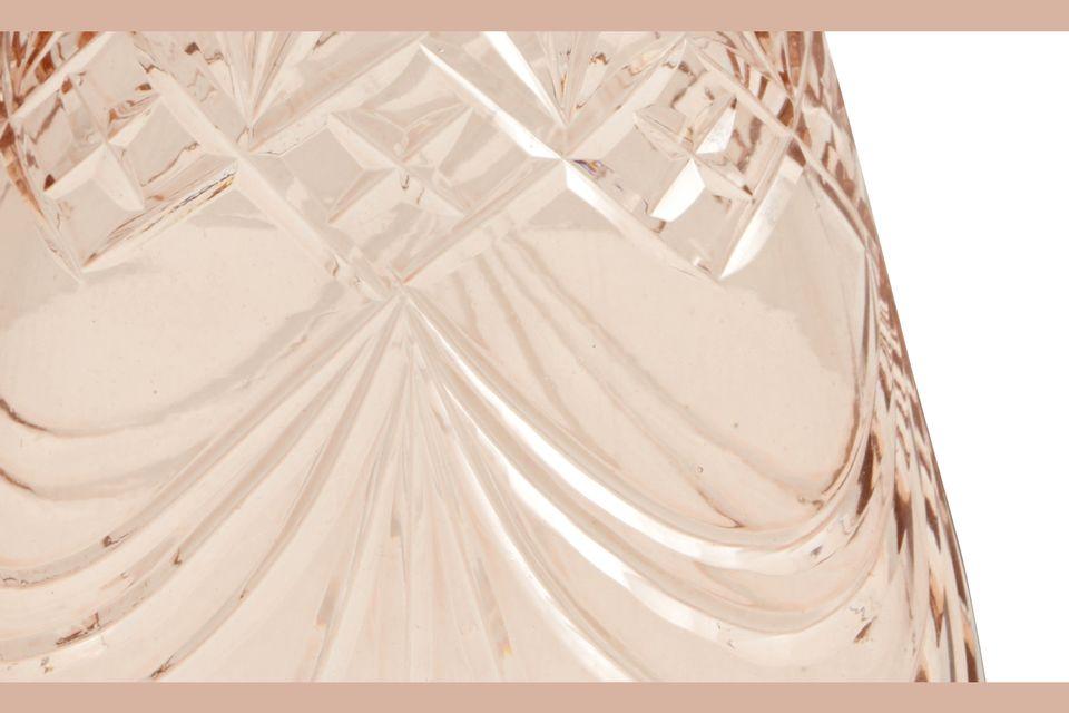 Su forma se estrecha hacia arriba para ser cubierta con un tapón redondeado cuyas facetas lo hacen