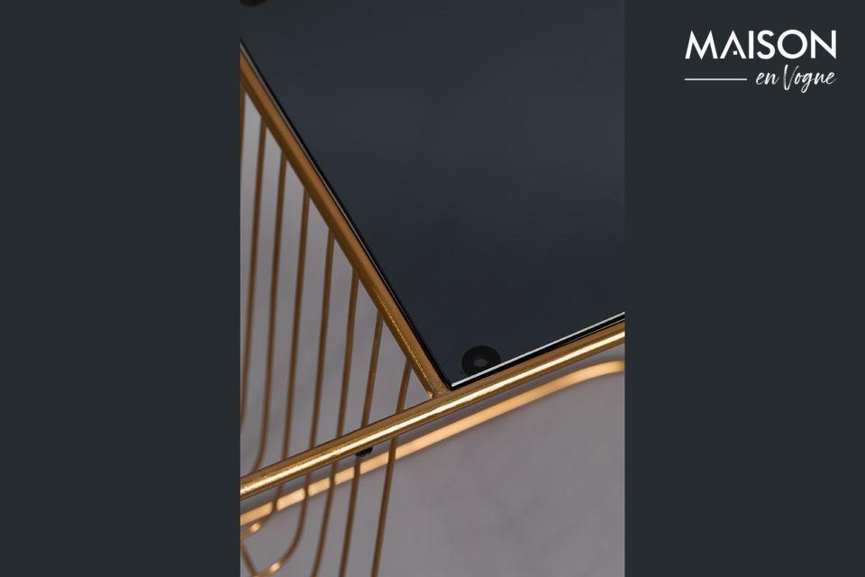 La muy delgada pata de metal dorado sigue la forma del tablero de la mesa