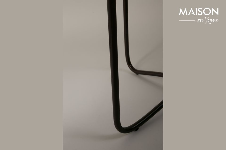 El tablero de la mesa se apoya en una base de metal negro que mejora el refinamiento de esta mesa