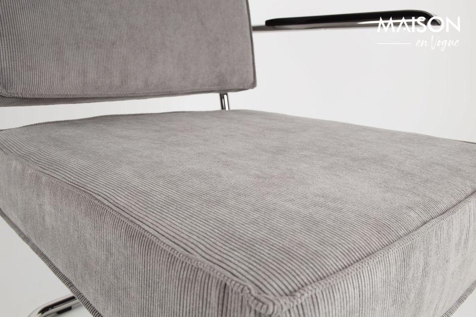 Su asiento y respaldo, estirados en pana gris claro, están generosamente tapizados