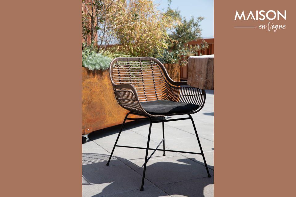 Este sillón retoma la tendencia de la moda retro con su cáscara de ratán sintético tejido