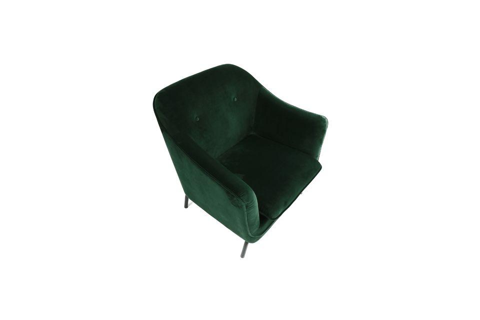 Un gran sillón de terciopelo verde oscuro con patas de metal.