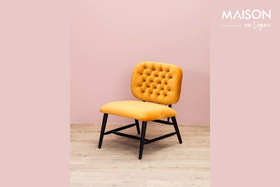 Un sillón de terciopelo con un respaldo tapizado de color ocre